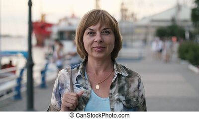 Cheerful blonde woman smiling and standing on Dnipro quay in...