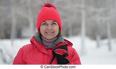 Cheerful blonde woman standing and smiling in a snowy pine forest in slow motion