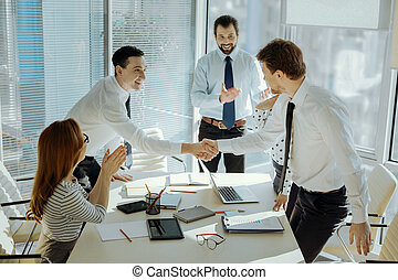 Cheerful boss introducing participants of business meeting