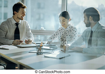 Cheerful boss joking with his colleagues during meetings