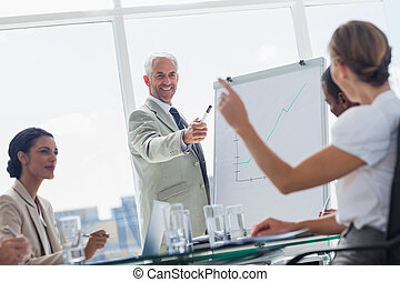 Cheerful boss pointing at a colleague