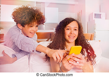 Cheerful boy and girl with cell phone on the sofa
