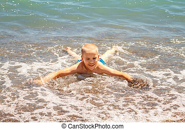 cheerful boy bathes in the sea waves