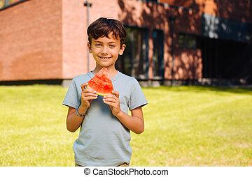 Cheerful boy eating a big slice of watermelon