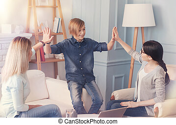 Cheerful boy giving high five to his mother and professional psychologist