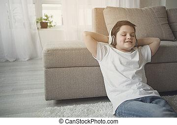 Cheerful boy listening favorite song from earphones -...
