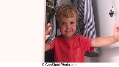Cheerful boy playing in wardrobe at home - Side view of...