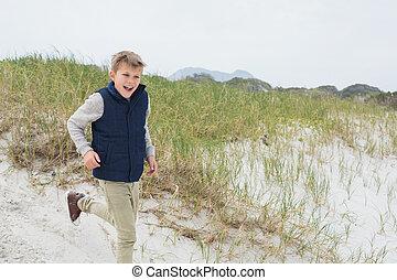 Cheerful boy running at beach