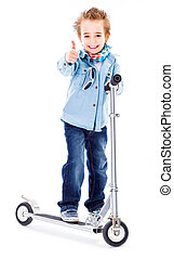 Cheerful boy showing thumbs up on scooter