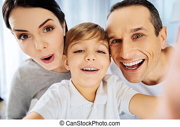 Cheerful boy taking close-up selfie with parents