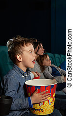 Cheerful boy watching film and expressing emotions in cinema.