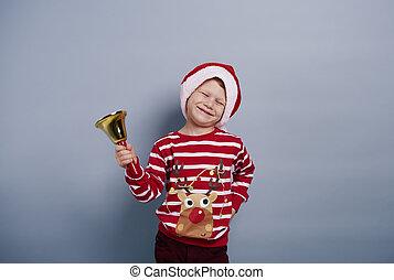 Cheerful boy with handbell at studio shot