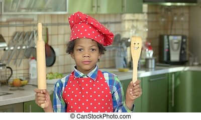 Cheerful boy with kitchen utensils. Mulatto kid in chef...