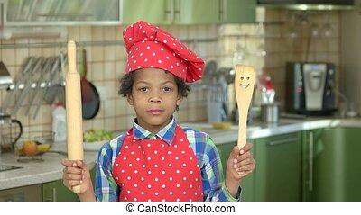 Cheerful boy with kitchen utensils. Mulatto kid in chef...
