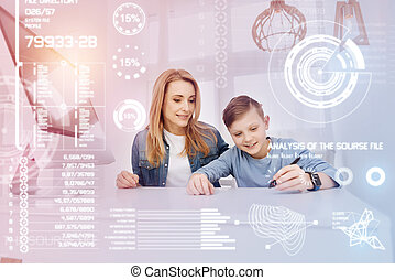 Cheerful boy working with stylus while his mother sitting near