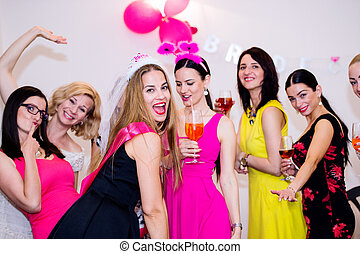 Cheerful bride and bridesmaids celebrating hen party with ...