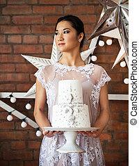 Cheerful bride holding wedding cake