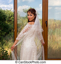 Cheerful bride in front of window