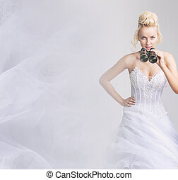 Cheerful bride looking through the binoculars