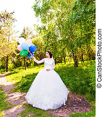 Cheerful bride posing with bunch of balloons