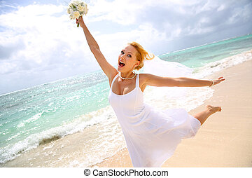 Cheerful bride showing happiness at the beach