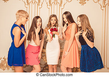Cheerful bride showing her surprised bridesmaids a wedding ring