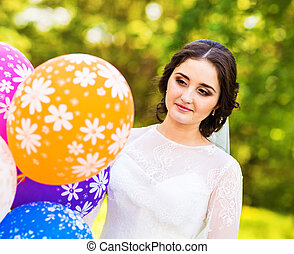 Cheerful bride with bunch of balloons