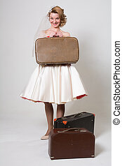 Cheerful bride with suitcases