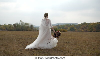 Cheerful bride with wedding bouquet spins around in Slow Motion on a fantastic autumn meadow against colorful Forest and Beautiful nature landscape.