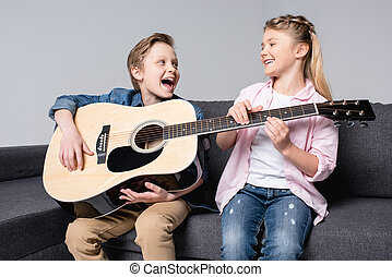 cheerful brother and sister playing on guitar and singing together while sitting on sofa