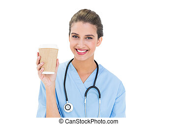 Cheerful brown haired nurse in blue scrubs holding a cup of coffee on white background