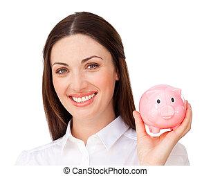 Cheerful brunette businesswoman saving money in a piggybank