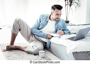 Cheerful brunette male making notes