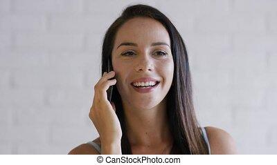 Cheerful brunette speaking on phone