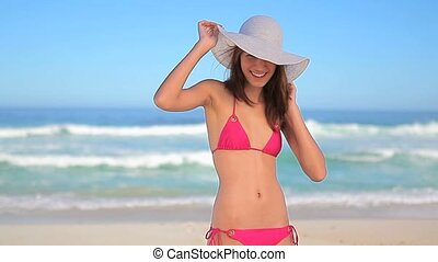 Cheerful brunette throwing her hat