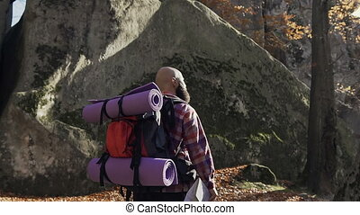 Cheerful brunette tourist man wears a shirt ina cages and backpacked have walk through forest, autumn tourism concept. Rocks in the mountains. Autumn