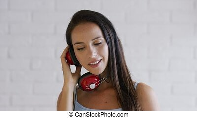 Cheerful brunette with headphones - Attractive young lady...