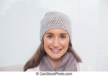 Cheerful brunette with winter hat on posing