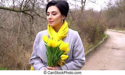 Cheerful brunette woman enjoying smell of yellow tulips...