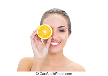 Cheerful brunette woman holding an orange half in front of her eye on white background