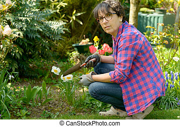 Cheerful brunette woman planting flowers in garden
