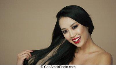 Cheerful brunette woman touching hair