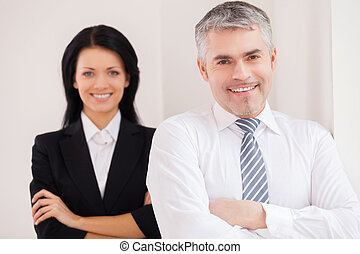 Cheerful business colleagues. Confident senior man in shirt and tie looking at camera and keeping arms crossed while woman standing on background