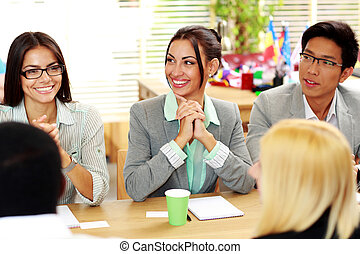 Cheerful business people sitting around the table at the meeting
