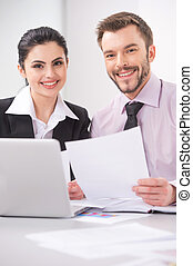 Cheerful business people sitting at table with laptop. Young...