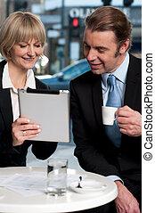 Cheerful business people using digital tablet