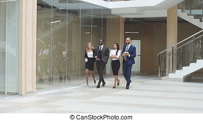 Cheerful business people walking together along the office corridor and holding a conversation. Slow motion