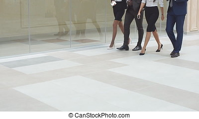 Cheerful business people walking together along the office corridor. Slow motion