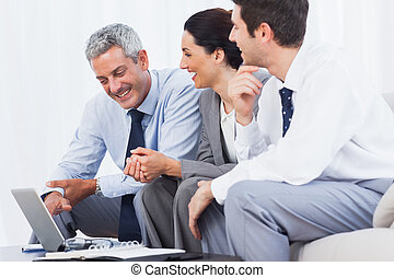 Cheerful business people working with their laptop on sofa