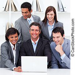 Cheerful business team looking at a laptop